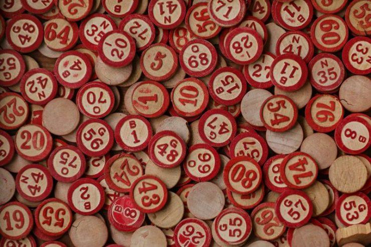 Koleksi koin bingo kayu yang dicat dengan angka merah.