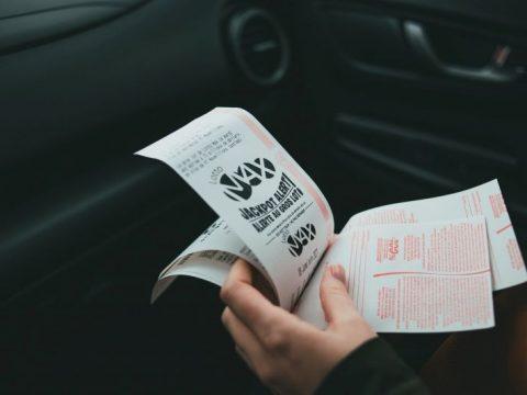 Sebuah tangan memegang tiket lotere, di dalam mobil.