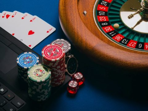 Keripik dan kartu duduk di sebelah roda roulette.